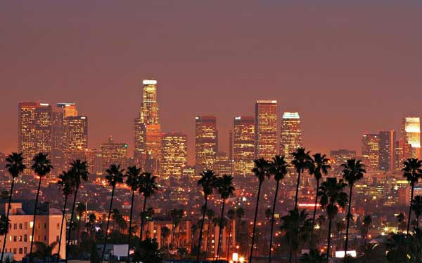 Los Angeles skyline at sunset with palm trees