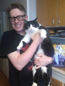 Man holds long black and white cat