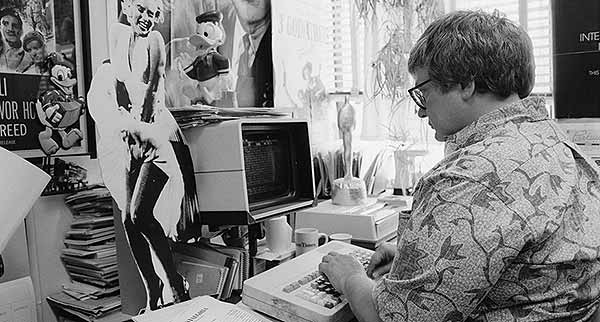 Roger Ebert typing on a computer in his office